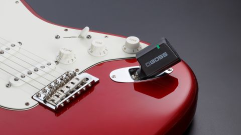 Boss WL-50 review: Boss WL-50 transmitter plugged into a red Fender Stratocaster on a grey background