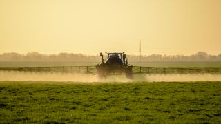 A tractor spraying chemicals on a field.