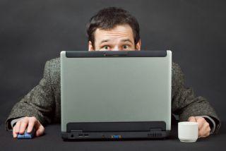 Man peering over computer