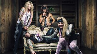 A press shot of Steel Panther lying on a sofa