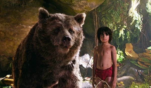 Disney's The Jungle Book Baloo and Mowgli stand underneath some rocks