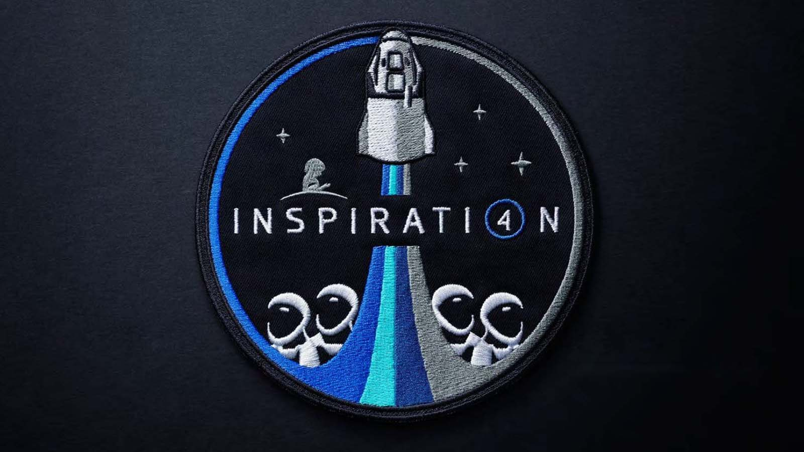 The Inspiration4 Mission Patch Against A Dark Gray Background