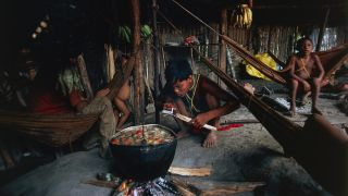 Yanomami men and children cook together in a hut in the Amazon rainforest.