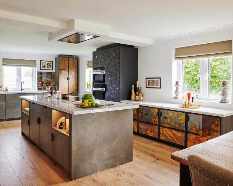 Wood kitchen flooring in a white scheme with dark stone cabinetry and a kitchen island.