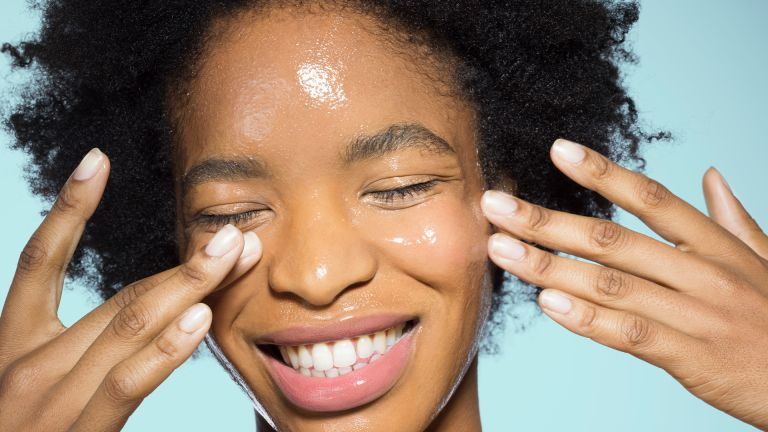 Young female applying glossy make-up - stock photo