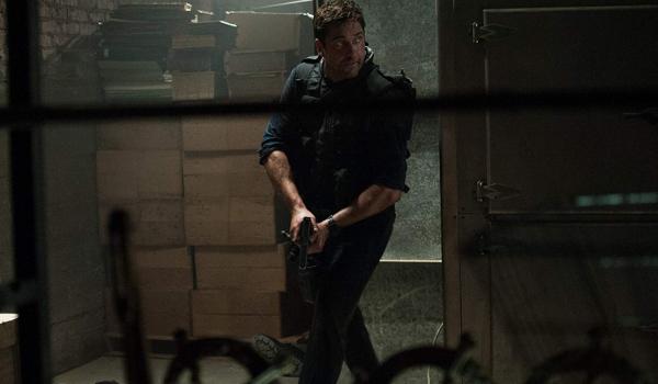 Olympus Has Fallen Gerard Butler patrols a hallway with a gun