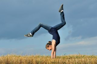 A teen girl does a handstand in a meadow.