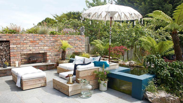 Tropical garden ideas shown in an exotic garden scene with corner sofa and parasol
