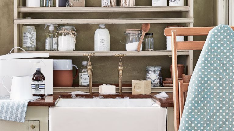 An example of utility room shelving ideas showing simple wooden shelves sat behind a faucet
