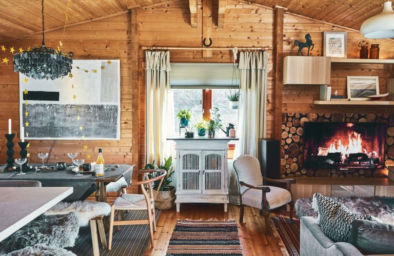 An open-plan living and dining space set in a fully-panelled log cabin