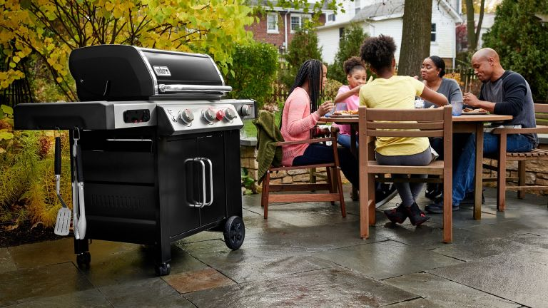 The best gas barbecue hero image showing a Weber Genesis II EX-335 GBS Smart Barbecue in front of a group of people sat around a table outside enjoying a meal