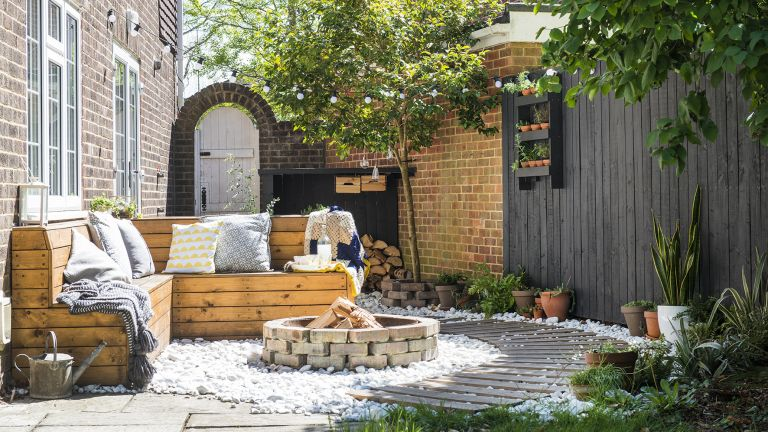 Small garden with wooden outdoor seating, fire-pit and wooden boardwalk on white gravel, black wooden fence.