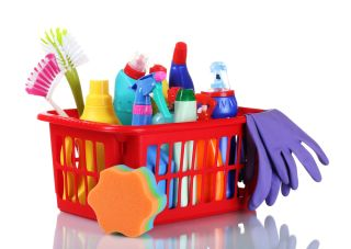A box of household cleaning products, including spray bottles, sponges and scrubbers.