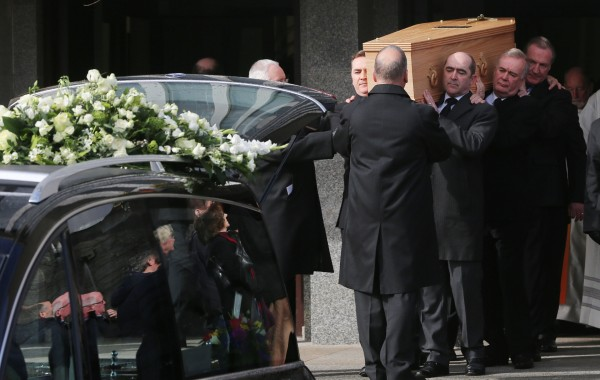 Pallbearers carry the coffin of the late actor Frank Kelly