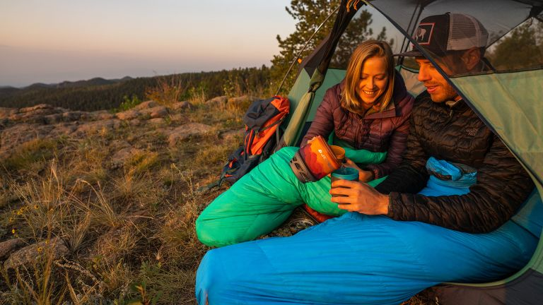 Man and woman sitting in open tent in their Kelty Cosmic Ultra 20F sleeping bags
