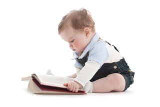 A baby sits looking at a book.
