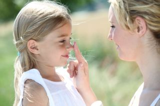 A mom taps her daughter on the nose.