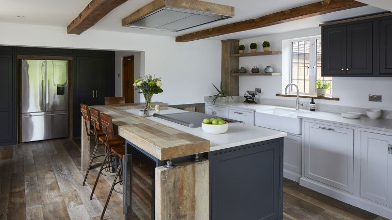 A kitchen with blue-grey island with reclaimed wood-topped breakfast bar, exposed wooden beams on a white ceiling, and white quartz worktops over pale grey cabinets