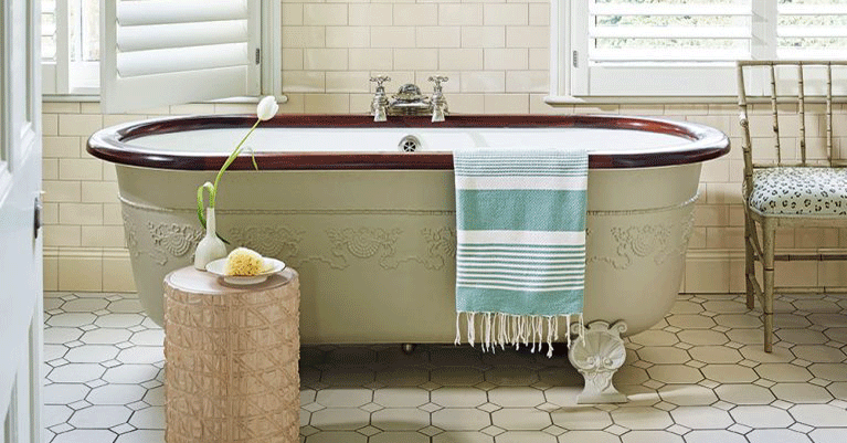An example of bathroom flooring ideas showing a free-standing bath with a striped towel hanging on the edge