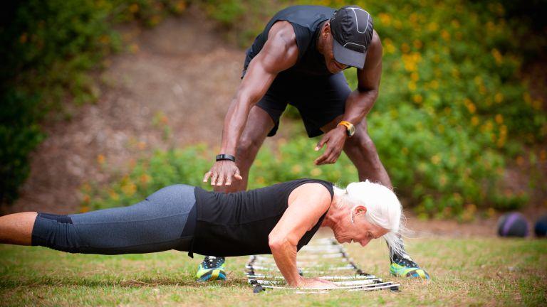 Senior woman being coached through push ups