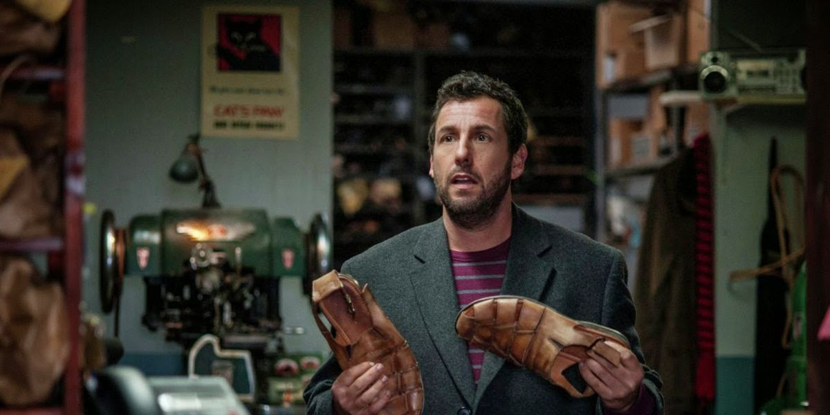 Max Simkin (Adam Sandler) holds a pair of shoes and looks confused in a scene from 'The Cobbler'