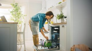 Woman loading a dishwasher in the kitchen