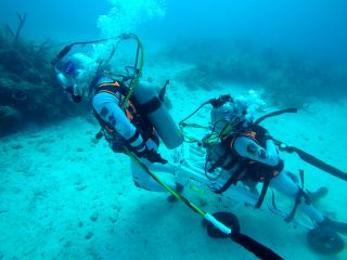 NASA astronaut Kjell Lindgren pulled ESA astronaut Pedro Duque during a simulated moonwalk beneath the Atlantic Ocean. The pair tested a new instrument that allows for the safe and rapid transfer of a fallen companion despite the bulkiness of spacesuits.