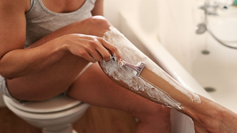 Woman in bathroom using a razor and shaving foam to shave her leg