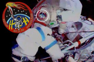 Cosomonaut Oleg Kotov can be seen wearing artist Luc van den Abeelen's Olympic torch patch while holding the real Sochi torch on a spacewalk outside the International Space Station, Nov. 9, 2013.