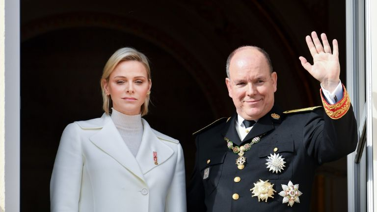 Princess Charlene of Monaco and Prince Albert of Monaco waving at a crowd.