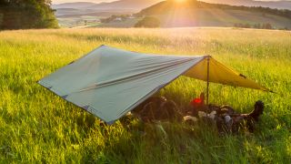 a tarp stretched over camping equipment in a field
