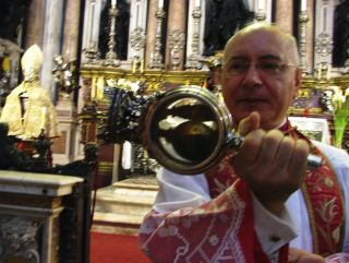 "During the ""blood miracle"" ceremonies (this photo from 2013), the archbishop of Naples shakes a vial of San Gennaro's ""blood,"" a solid mass, to see if it turns into liquid."