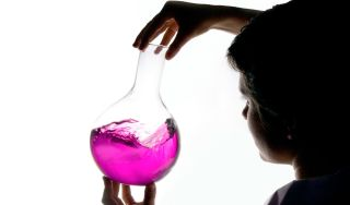 Child holding glass beaker filled with pink liquid.