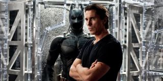Christian Bale as Bruce Wayne in front of his batsuit in The Dark Knight