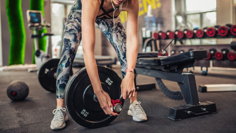 Woman changing weight plates on a barbell and securing them using a clamp