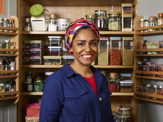 Smiling Nadiya Hussain in front of a wall of spices