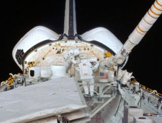 Kathy Sullivan and Dave Leestma work on the orbital refueling experiment during a spacewalk.