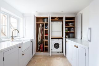 a utility room idea with all appliances and storage behind cabinet doors