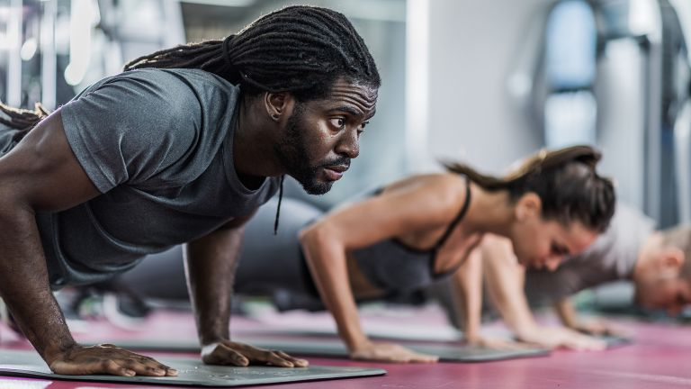 Man and woman doing push-ups in the gym during an AMRAP workout