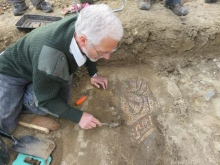 A Boxford volunteer begins to uncover the mosaic.