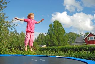 A girl bounces on a trampoline