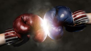 A close-up of a two boxing gloves hitting each other, one is red and the other blue to represent Republicans and Democrats, respectively.