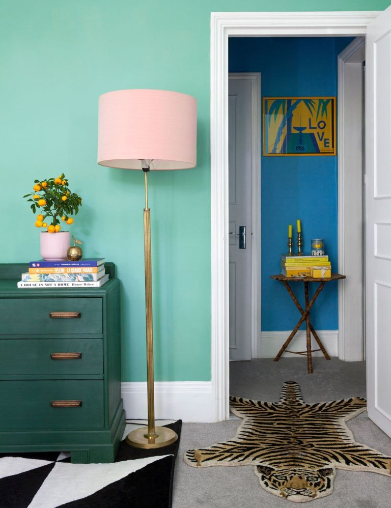 painted green bedroom with dark green cabinet and pink lampshade