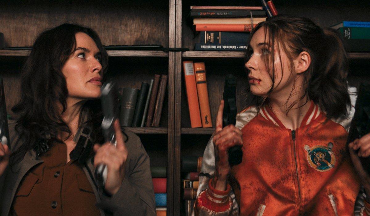 Lena Headey and Karen Gillan prepare their guns behind a bookcase in Gunpowder Milkshake.