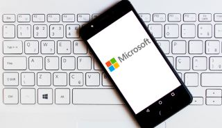 Microsoft logo displayed on an Android smartphone resting on the keyboard of a Windows laptop.