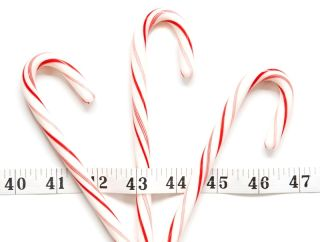 Candy canes sit on a table with a measuring tape over them.