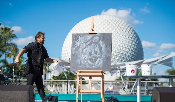 An Artist drawing Donald Duck in front of Spaceship Earth