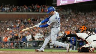 Cody Bellinger #35 of the Los Angeles Dodgers hits an RBI single to score Justin Turner #10 against the San Francisco Giants during the ninth inning in game 5 of the National League Division Series at Oracle Park on Oct. 14, 2021 in San Francisco, California.
