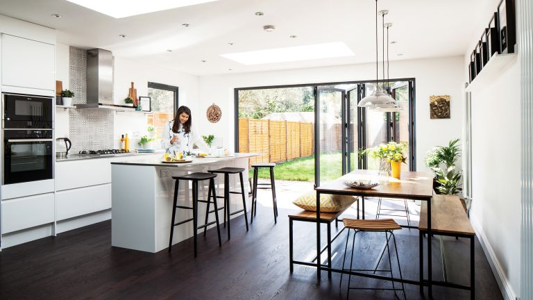 white light-filled kitchen extension with industrial style seating and dining table