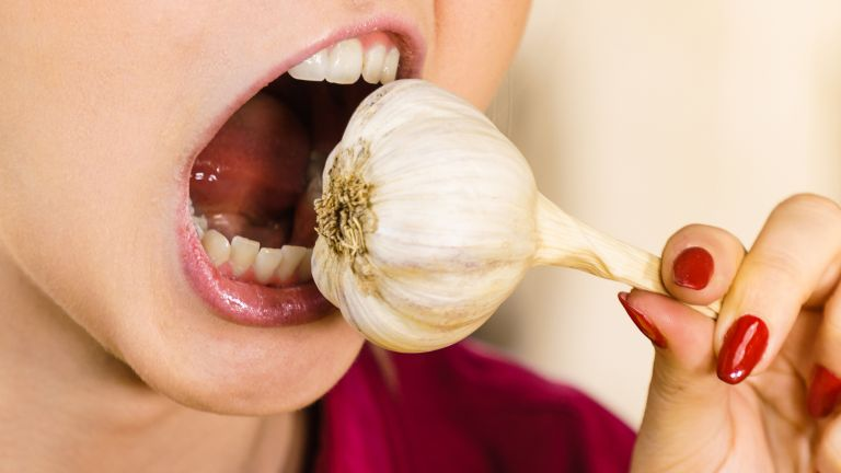 Close up of a mouth about to bite into a whole bulb of garlic